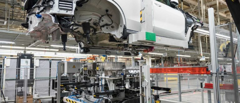 A BMW SUV battery being prepared on the assembly line.