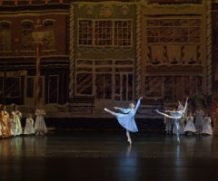 Dancers in blue dresses on a stage.