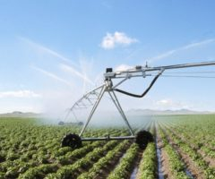 A mobile irrigation system spraying a large field on a farm.