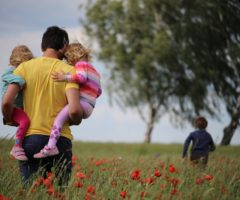 A parent holding two children in a flower field.