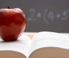 An apple and book in front of a chalk board.