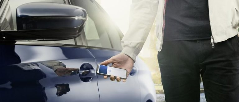A person unlocking a car door with their phone.
