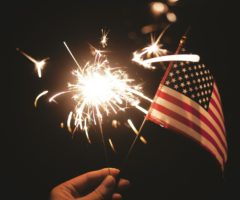A person holding a sparkler and American flag.