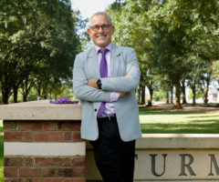 A man in a suit in front of a Furman University sign.