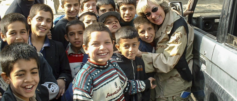A woman in a service uniform hugging a group of children.