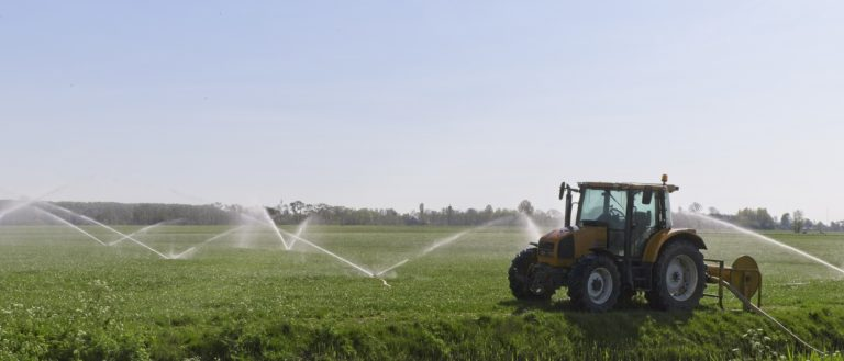 Sprinklers on a farm with a tractor in the foreground.