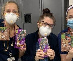 Health care workers holding girl scout cookie boxes.