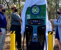 People unveiling an electric vehicle charger at a park.