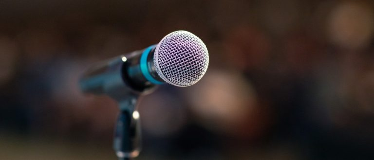 A microphone in front of a blurred crowd.