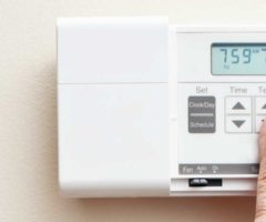 A person's hand adjusting a thermostat.