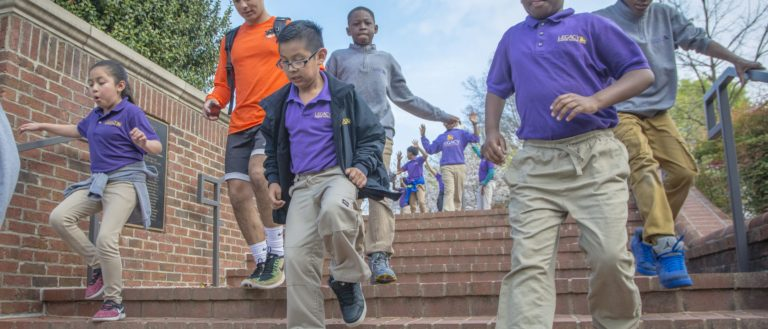 A group of children running down stairs outdoors.