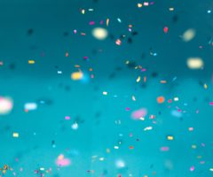 Confetti flying in front of a light blue wall.