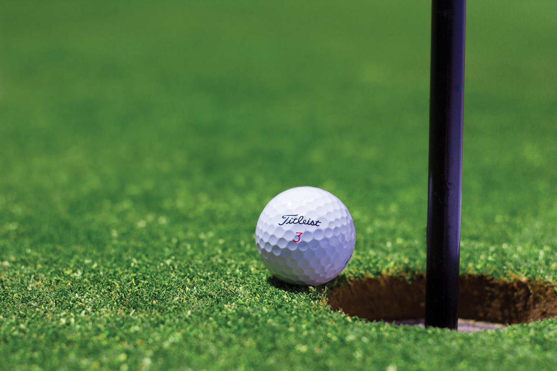 A golf ball inching towards a hole.