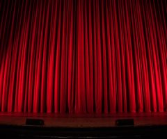 A red theatre curtain on stage.