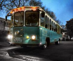 A light blue trolley on a street at dusk.