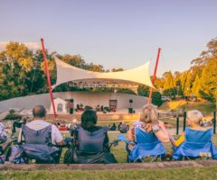 People seated at Barnet Park listening to a band performing on stage.