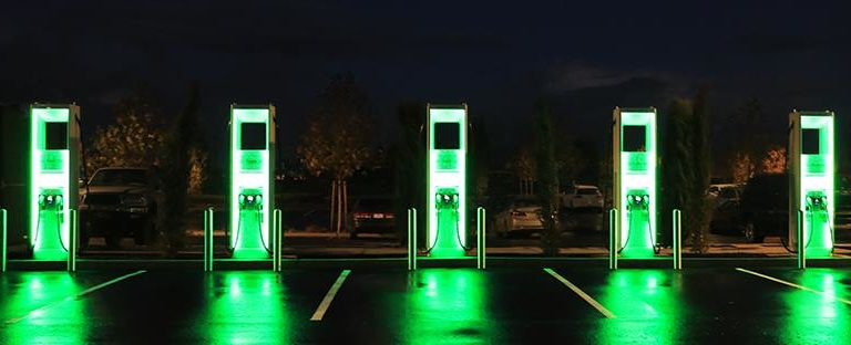 Electric vehicle charging stations lit up in green at night.