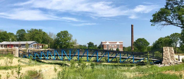 A blue and black bridge running through a greenway creek.