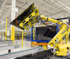 A robot lifting a solar panel in a warehouse.