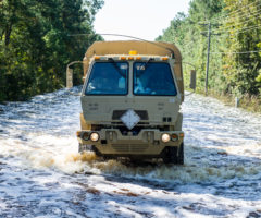 A large beige truck plowing through flooded waters.