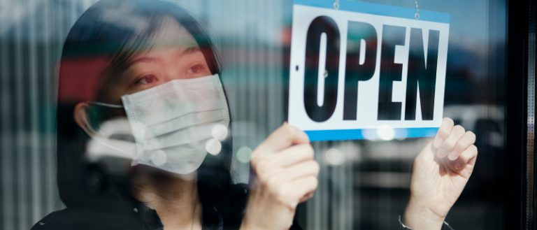 A person wearing a mask placing an open sign on a door.