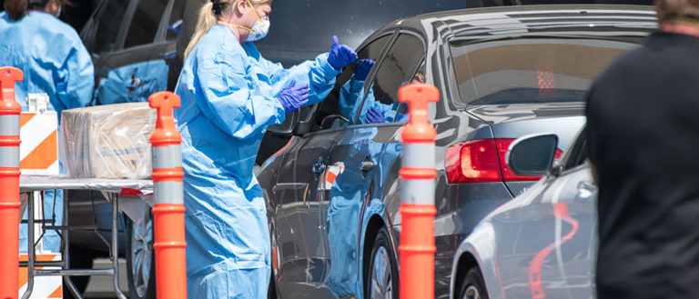 A person in a medical gown standing next to a car.