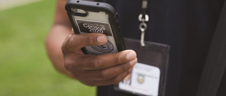 A person holding a Census-labeled phone.