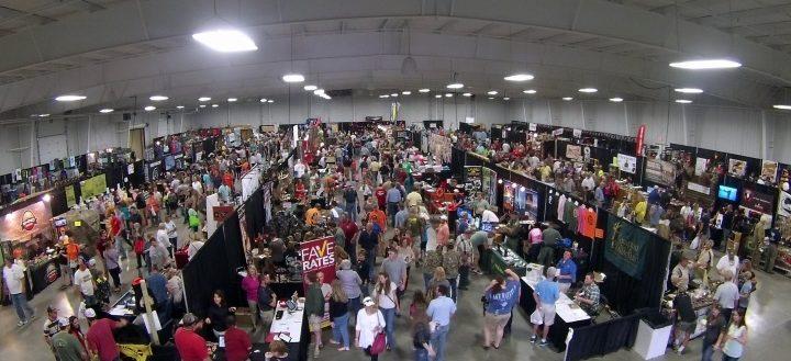 Hundreds of people walking through an exhibit floor.
