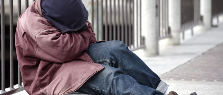 A person with baggy clothes resting on the sidewalk.