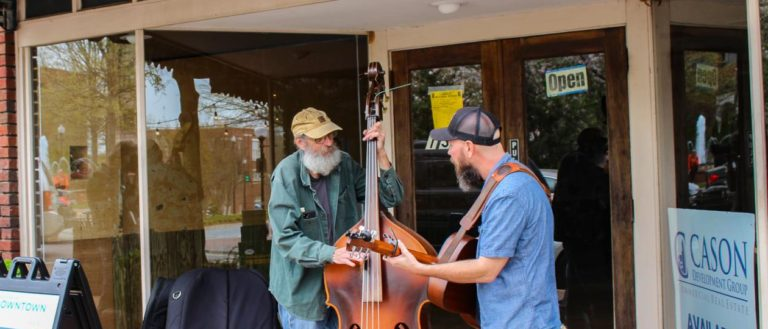 Two musicians playing in front of a glass windowed storefront.