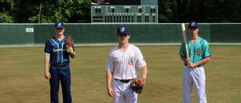 Three baseball players standing in the outfield.