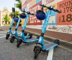 Four blue electric scooters in a parking space.