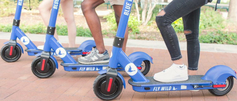 Three people standing on blue scooters.